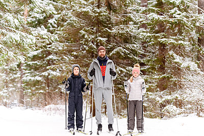Father and children skiing against trees in forest during winter - p300m2251494 by Ekaterina Yakunina