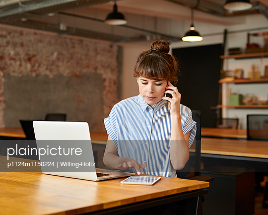 Junge Frau telefoniert am Arbeitsplatz - p1124m1150224 von Willing-Holtz