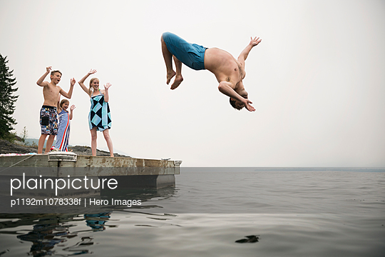 Family cheering father doing backflip into lake - p1192m1078338f by Hero Images