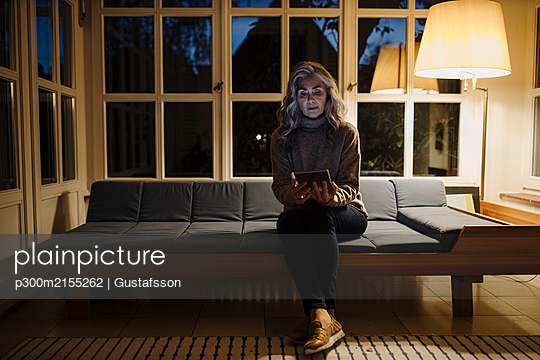 Mature woman using tablet on couch at home in the dark - p300m2155262 by Gustafsson