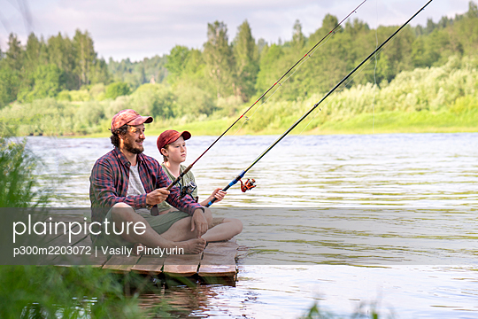 Father and son fishing while sitting on boardwalk at riverbank - p300m2203072 by Vasily Pindyurin