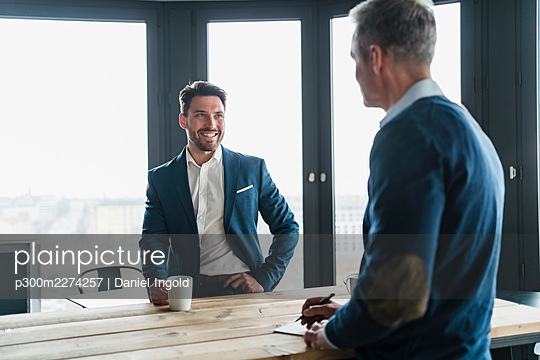 Smiling businessman having coffee while looking at male colleague in office - p300m2274257 by Daniel Ingold