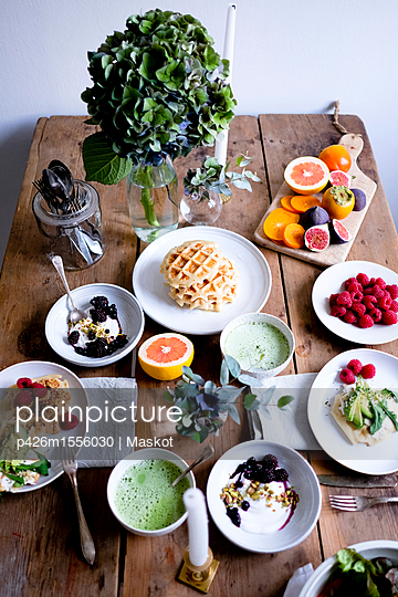 High angle view of various food on wooden table by wall - p426m1556030 by Maskot