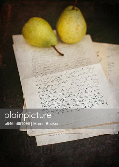 Zwei Birnen auf einem Stapel alter Briefe - p946m951096 von Maren Becker