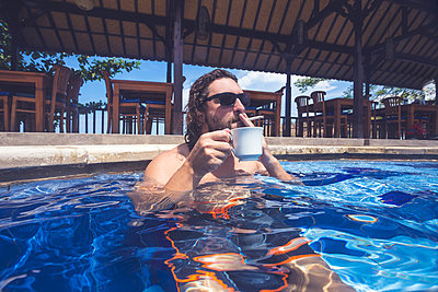 Young man with coffee and cigarette in pool - p1108m1104579 by trubavin