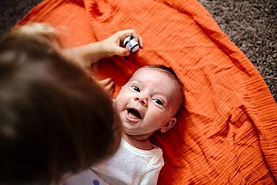 Laughing infant lying on orange blanket on floor - p1166m2148727 by Cavan Images