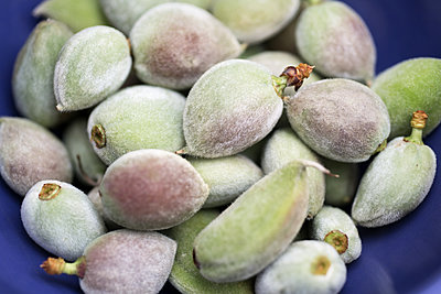 Green almonds in a bowl - p1580m2191503 by Andrea Christofi