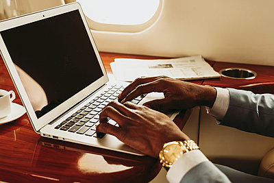 Businessman's hands typing on laptop in private jet - p300m2257061 by OneInchPunch