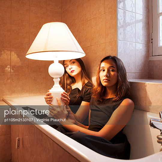 Two women with lamp in bathtub - p1105m2133107 by Virginie Plauchut