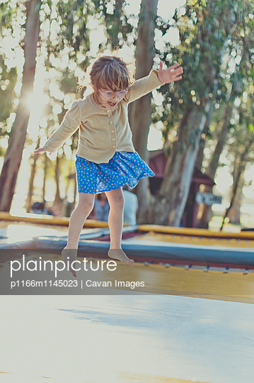 Full length of girl jumping on trampoline at playground - p1166m1145023 by Cavan Images