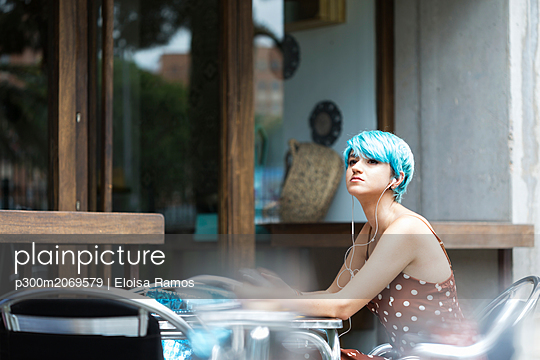Portrait of young woman with blue dyed hair sitting in a pavement cafe listening music with earphones - p300m2069579 by Eloisa Ramos