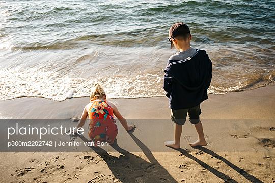 Siblings enjoying on shore at beach - p300m2202742 by Jennifer van Son