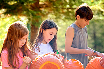 Three Young Children Carving Pumpkins Outdoors - p1166m2147189 by Cavan Images
