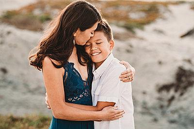Loving mother embraces smiling preteen son - p1166m2207854 by Cavan Images