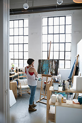 Female painter with palette examining canvas painting on easel in art studio - p1192m1490239 by Hero Images