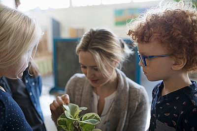 Preschool teacher and students examining potted plant - p1192m1560148 by Hero Images