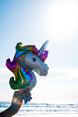 Unicorn balloon on the beach - p1423m2002069 by JUAN MOYANO