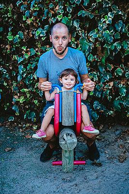 Baby girl and father enjoying at playground while riding a wooden motorbike - p300m2024136 von Gemma Ferrando