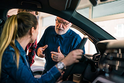 Car dealer showing car to couple in showroom - p300m2167398 by Robijn Page