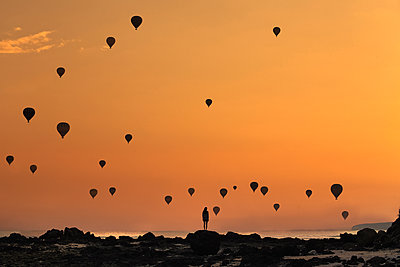 Indonesia, West Nusa Tenggara, Silhouettes of hot air balloons flying over lone woman standing on rocky shore at moody dusk - p300m2199179 by Konstantin Trubavin
