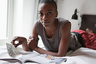 Portrait of young woman with magazine lying in bed at home - p301m961067f by Halfdark