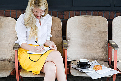 Woman writing outside coffee shop - p9245404f by Image Source