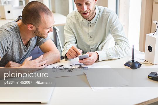 Zwei Studenten schauen auf ein Smartphone - p1284m1452087 von Ritzmann