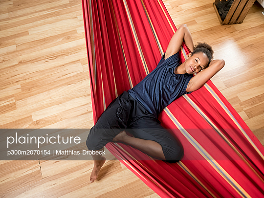 Overhead view of young woman lying in hammock - p300m2070154 by Matthias Drobeck