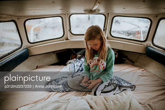 Girl on boat using cell phone - p312m2237233 by Anna Johnsson