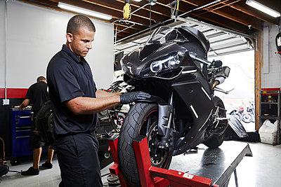 Colleagues making motorcycle in factory - p1166m1209888 by Cavan Images
