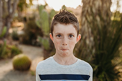 Close up portrait of cute young boy with freckles making funny face - p1166m2136645 by Cavan Images