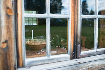 Blick durch das Fenster in eine Blockhütte - p271m1194643 von Michael Jörrn