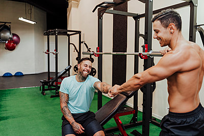 Male friends giving fist bumps by exercise equipment in gym - p300m2274497 by Eva Blanco