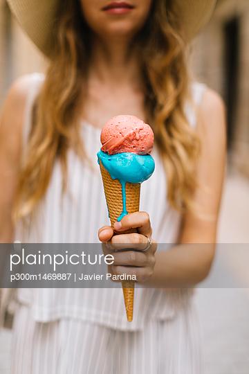 Woman holding melting ice cream cone - p300m1469887 by Javier Pardina