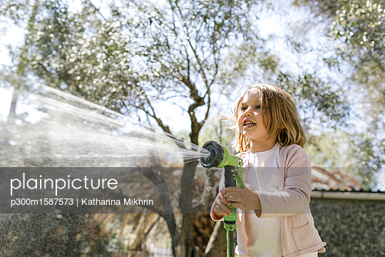 Smiling little girl playing with garden hose - p300m1587573 von Katharina Mikhrin