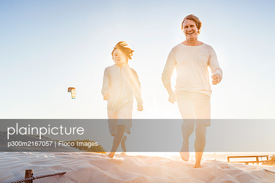 Father having fun with his son on the beach, running in the sand - p300m2167057 by Floco Images