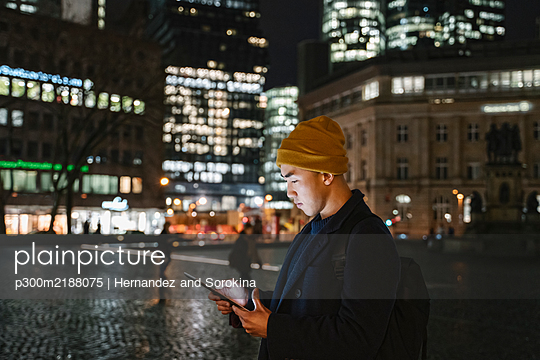 Man using tablet in the city at night - p300m2188075 by Hernandez and Sorokina