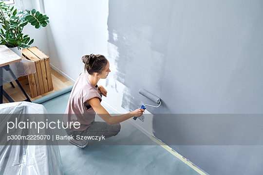 Young woman with paint roller painting wall while crouching at home - p300m2225070 by Bartek Szewczyk