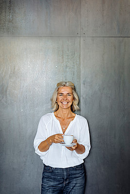 Portrait of a happy casual mature businesswoman standing in front of a grey wall holding coffee cup - p300m2144784 by Sofie Delauw