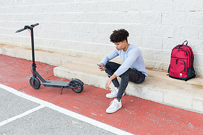 Young man with e-scooter and smartphne outdoors - p300m2156362 by Sus Pons