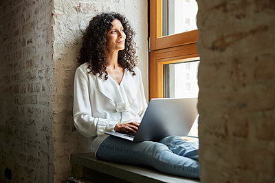Businesswoman day dreaming while sitting with laptop on window sill - p300m2293758 by Rainer Berg