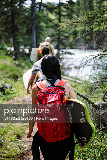 Surfer friends walking with surfboards in sunny woods - p1192m2129166 by Hero Images