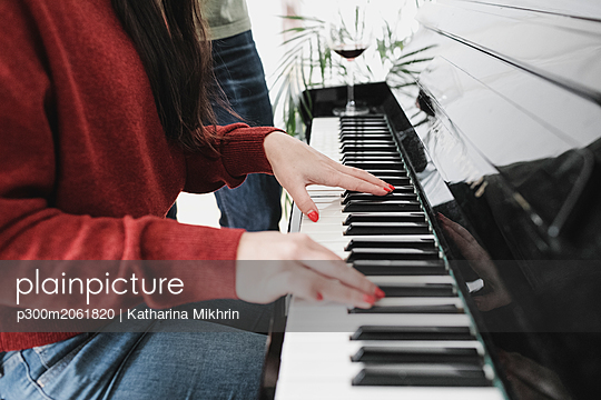 Hands of a woman playing the piano at home - p300m2061820 by Katharina Mikhrin