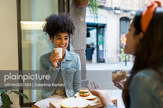 Female friends talking while having food and drink sitting by window at cafe - p300m2227293 by Valentina Barreto