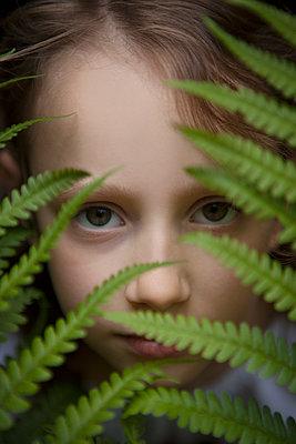 Mädchen versteckt sich hinter Farn - p045m1460765 von Jasmin Sander