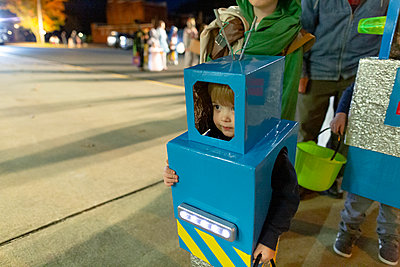 Child in homemade robot costume stands in line for trick-or-treating - p1166m2153298 by Cavan Images