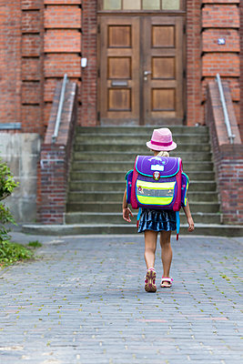 Back view of little girl with school bag in front of her school - p300m1228522 by Jana Fernow