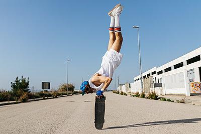 Man in stylish sportive outfit standing on skateboard upside down - p300m2029462 von Josep Rovirosa