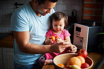 Father and baby girl eating fruit in kitchen at home - p300m2078605 by gpointstudio