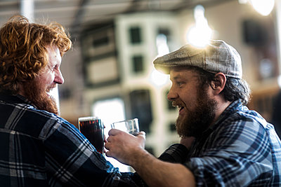 Male customers laughing in traditional Irish public house - p429m2068910 by Sigrid Gombert